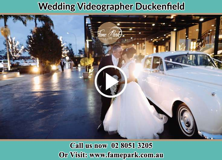 The newlyweds kissing near the wedding car Duckenfield NSW 2321