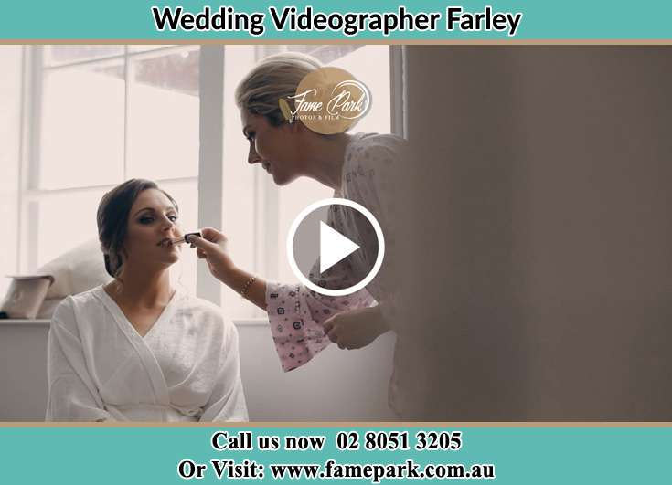 A woman applying lipstick to the Bride Farley NSW 2320