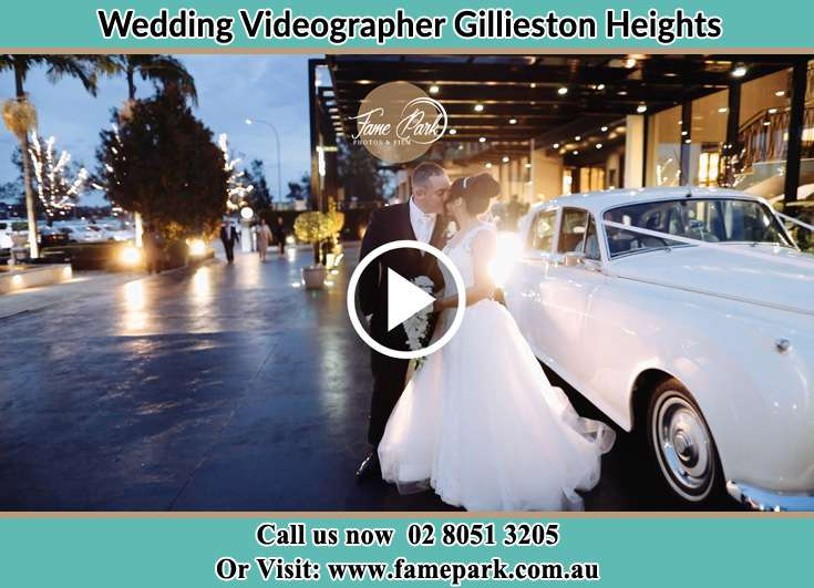 The newlyweds kissing near the wedding car Gillieston Heights NSW 2321