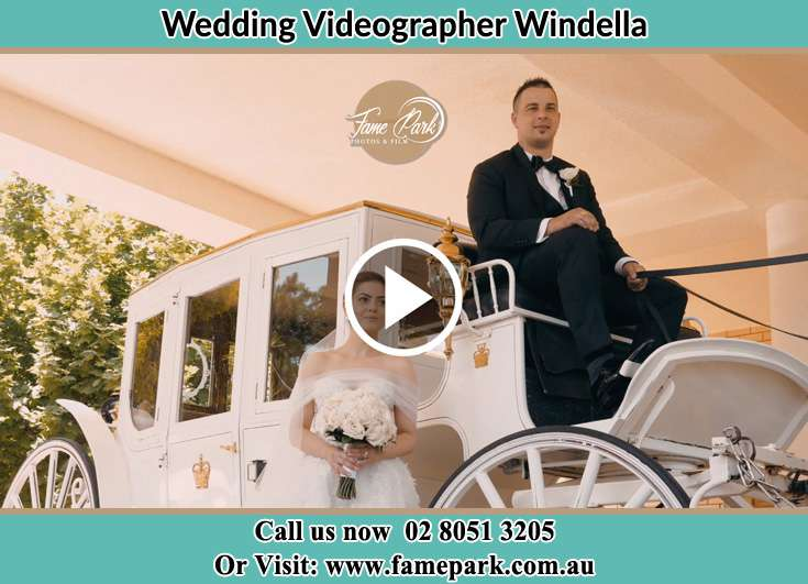 The newlyweds pose for the camera with the wedding carriage Windella NSW 2320
